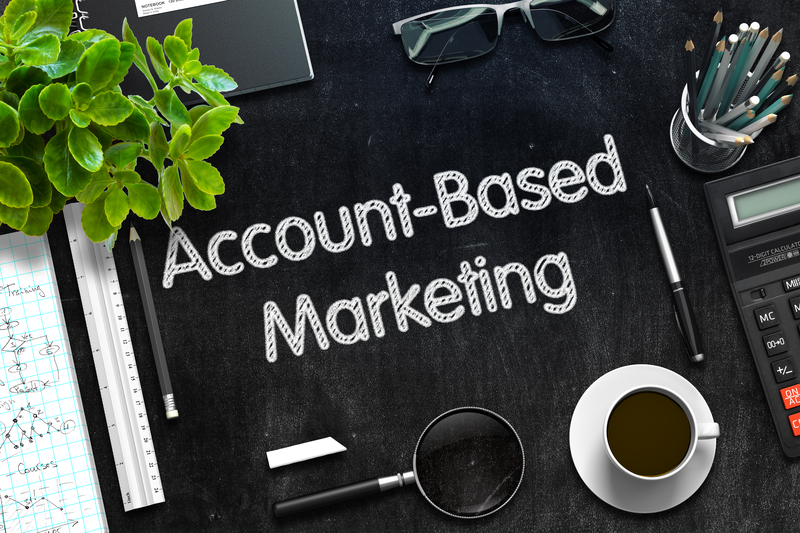 Account based marketing spelt out on a chalk board, next to a cup of coffee.