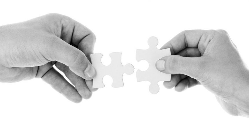 Two hands joining two puzzle pieces together.