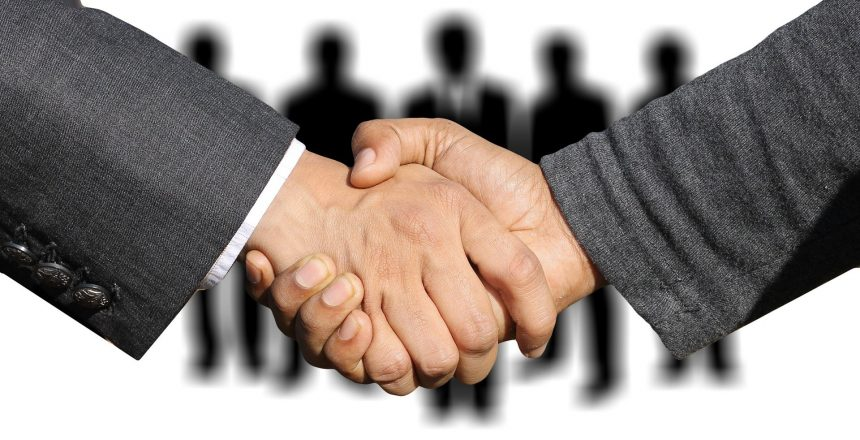 two people wearing suits, shaking hands.
